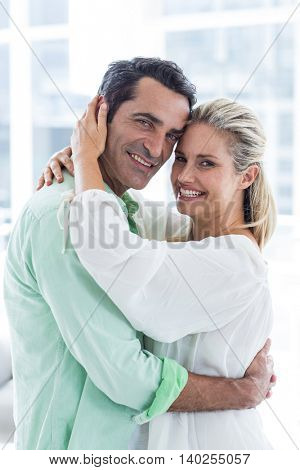 Portrait of mid adult romantic couple embracing at home