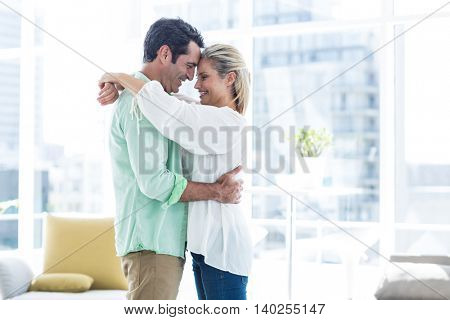 Side view of mid adult romantic couple hugging at home