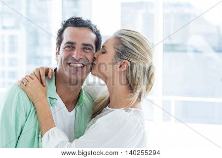 Mid adult romantic woman kissing man at home