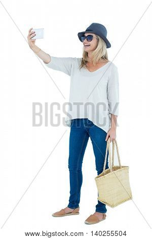 Cheerful mid adult woman taking selfie against white background