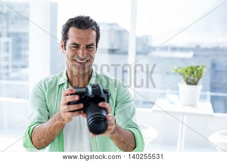 Mid adult man holding camera while sitting at home