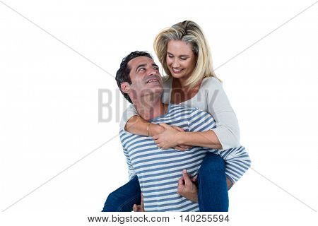 Romantic mid adult man carrying woman piggyback against white background