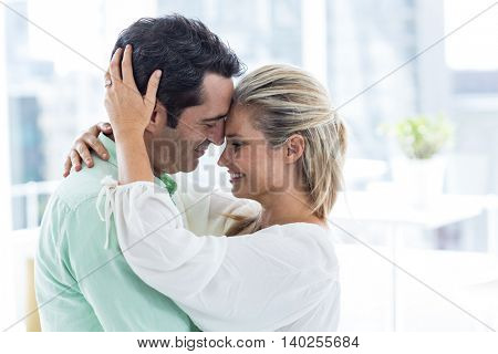 Mid adult romantic couple embracing at home