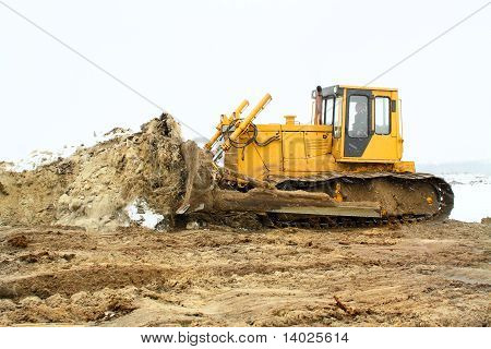 A Yellow Bulldozer Working In The Winter