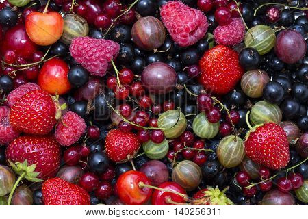 berry background with fresh raspberries, blueberries, currants, strawberries, cherries,