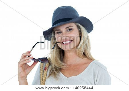 Portrait of mid adult woman holding sunglasses against white background