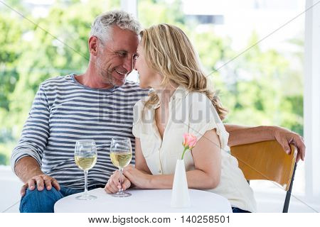 Romantic mature couple with white wine while sitting at restaurant