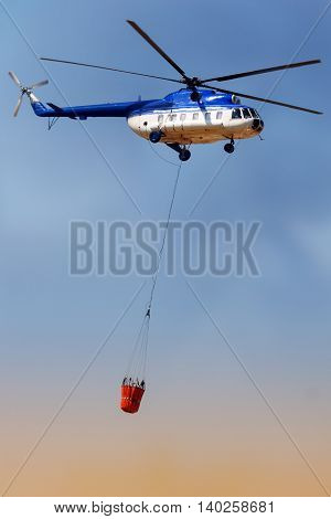 Blue fire rescue helicopter with water bucket transportation