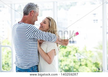 Romantic mature couple embracing while standing at restaurant