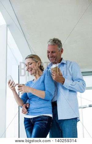 Low angle view of mature couple using phone while standing at home