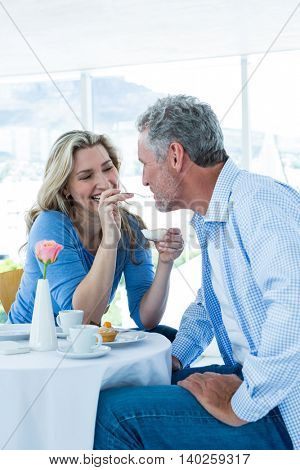 Smiling mature woman feeding food to man while sitting at restaurant