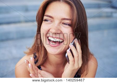 Happy young beautiful woman is laughing while talking on the phone on the street on a warm day