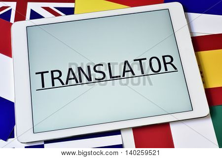the word translator in the screen of a tablet computer surrounded by flags of different countries