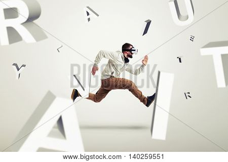 Young man in casual clothes and virtual reality glasses is running between 3d letters over white background