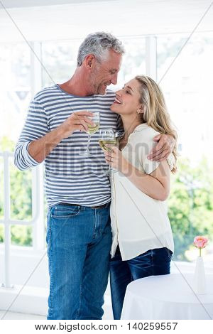 Romantic mature couple with wine glasses while sitting at restaurant