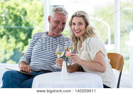 Portrait of smiling mature couple holding wine glasses at restaurant