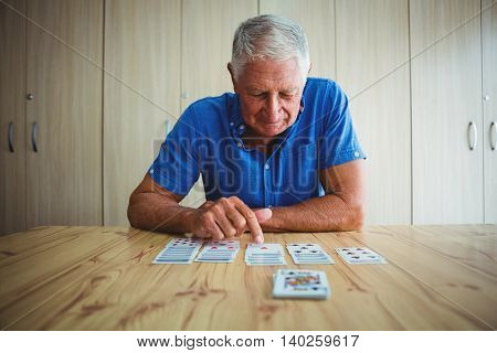 Senior man pointing at a card on a wooden table