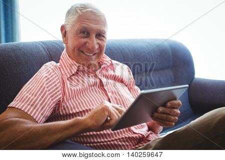 Senior man seated on a sofa looking at camera while holding digital tablet