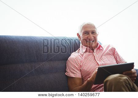 Senior man seated on a sofa while holding digital tablet and having leg crossed