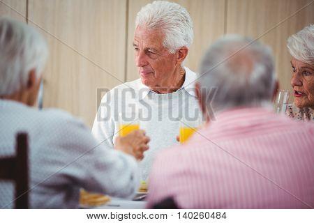 Senior people having an orange juice drink during the lunch