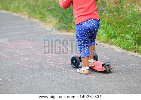 little girl riding scooter on playground outdoors
