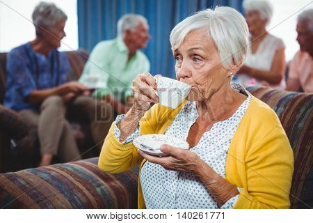 Senior woman drinking a cup of coffee looking away