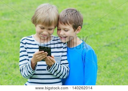 Children with mobile phone outdoor. Boys smiling, looking to phone, playing games or using application. Technology, education, leisure, people concept
