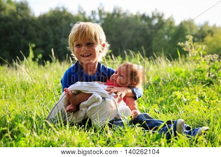 little boy holding newborn sister in summer nature, family love