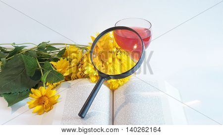 Book and yellow flowers and a white background next to a glass of red wine