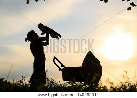 Silhouette of mother with little baby and stroller at sunset sky