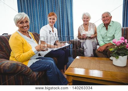 Senior persons and a nurse looking at camera in a sofa