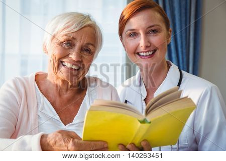 Nurse and senior woman reading book in a retirement home