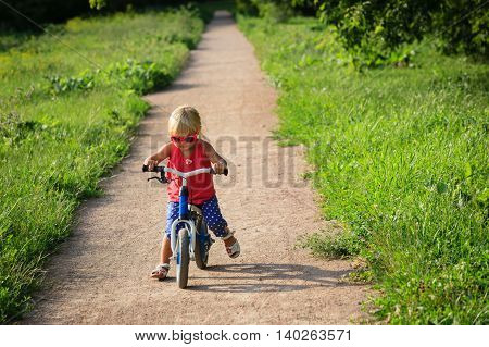 cute little girl riding runbike in summer, kids sport