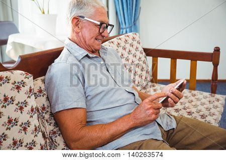 Senior man using a smartphone in a retirement home