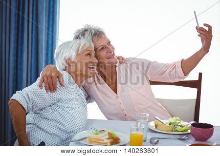 Senior woman taking a selfie during the lunch