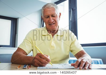 Senior man using a colouring book in a retirement home