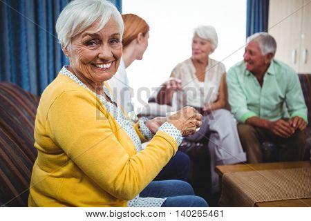 Senior person looking at camera with senior person chatting behind