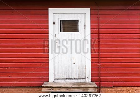 Small White Closed Door In Red Wooden Wall