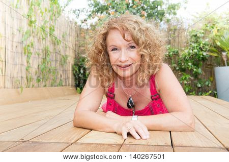 Blond Middle Aged Woman Laying On Pool Deck