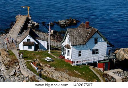 Boston Massachusetts - October 10 2008: Lighthouse keeper's home cottage and boat slip at the United States Coast Guard Lighthouse Station on a rocky coastal island in Boston harbour
