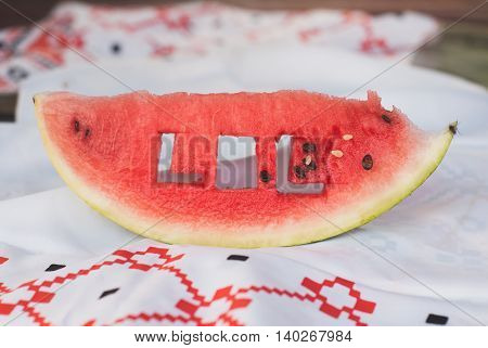 a fresh piece of watermelon and a tablecloth with a pattern on a wooden table