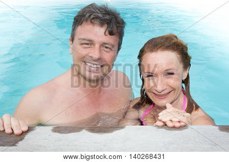 Middle Aged Couple Having Fun In The Water, Smiling At The Camera