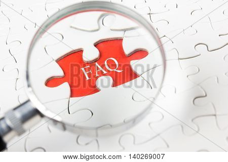 FAQ concept - Magnifying glass searching missing puzzle peace.