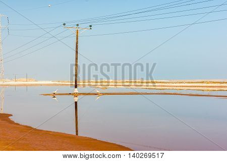 View of Dead Sea coastline with power line and mountains at sunny day in Israel