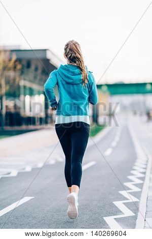 Rear view of woman running, toned image, vertical image