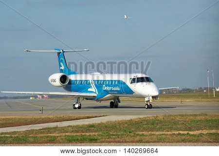 Borispol Ukraine - October 23 2011: Dniproavia Embraer ERJ-145 regional passenger plane is taxiing to the runway on sunny day