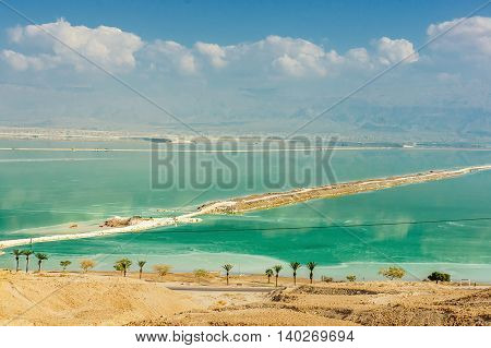 Aerial view of Dead Sea coastline with sand beach and road crossing water at sunny day in Israel