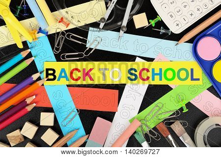 back to school concept with a variety of supplies on blackboard