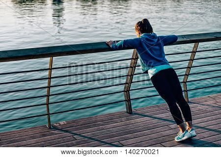 Woman doing push-ups outdoors, toned image, horizontal image