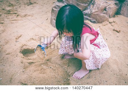 Adorable Asian Girl Has Fun Digging In The Sand On A Summer Day. Vintage Tone. Outdoors.